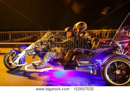 Kiyv Ukraine - October 01 2016: Couple of bikers riding through the night on the road shining tricycle