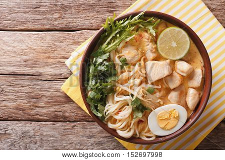 Malaysian Laksa Soup With Chicken, Egg, Noodles And Herbs Close Up In A Bowl. Horizontal Top View