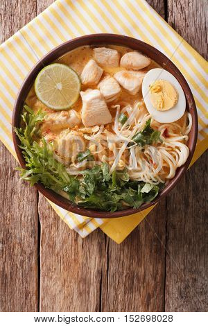 Malaysian Laksa Soup With Chicken, Egg, Noodles And Herbs Close Up In A Bowl. Vertical Top View