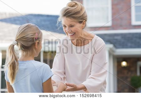 Cheerful grandmother welcoming granddaughter to her house. Senior healthy woman delighted to see little girl in the garden outside house. Older woman and grandchild in a happy conversation.