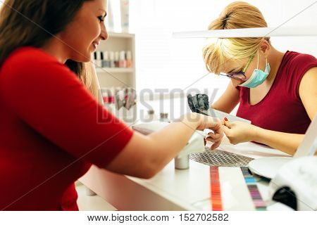 Manicurist working on client nails in professional salon