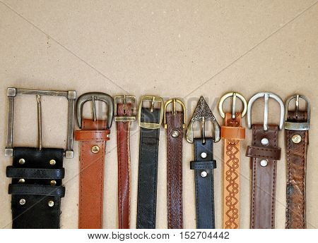Fashion background. Vintage brown leather belts with metal rusty buckle on beige cardboard surface closeup.