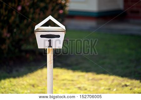 Australian home letterbox with number one on frontyard