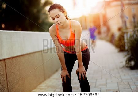 Fatigue of cute young beautiful female runner