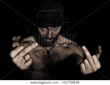 Dark portrait of scary evil sinister bearded man with smirk, showing middle finger. strange Russian man with a naked torso and a woolen hat