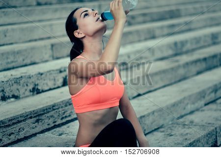 Thirsty cute sportswoman drinking water after workout