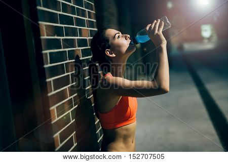 Thirsty young sportswoman drinking water after workout