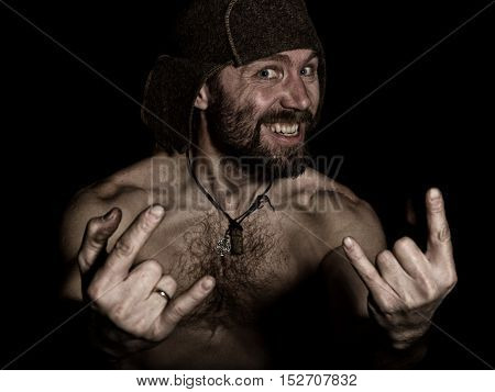Dark portrait of scary evil sinister bearded man with smirk, shows sign of heavy metal. strange Russian man with a naked torso and a woolen hat.
