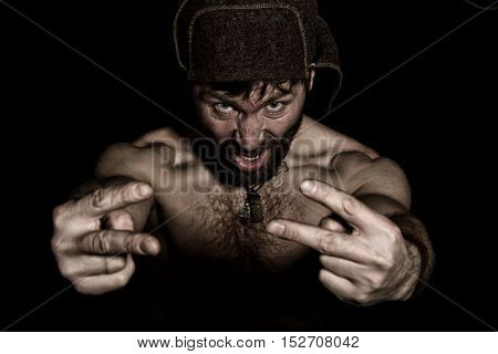 Dark portrait of scary evil sinister bearded man with smirk, shows sign of Victory. strange Russian man with a naked torso and a woolen hat.