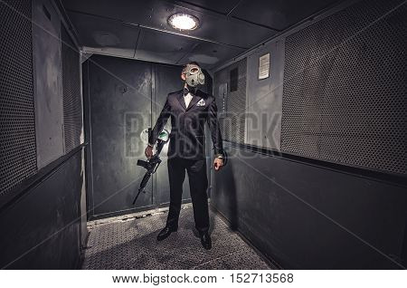 Man in gas mask and suit, standing in old elevator. Secret agent, terrorist or businessman of apocalypse?