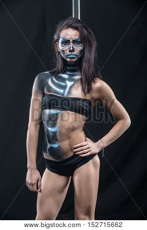 Sexy pole dancer in black sport underwear posing in front of a pylon in the studio on the dark background. She has a body-art on her body. Girl looks into the camera. Vertical.