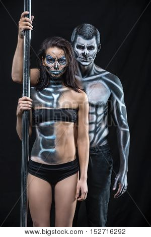 Two pole dancers with horrific body-art stands next to a pylon on a dark background in the studio. They dressed in black sportswear. Guy and the girl hold the right hands on the pylon. Vertical.