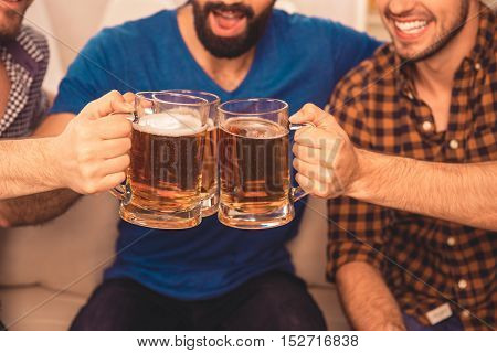 Close Up Portrait Of Three Happy Men Clinking With Glasses Of Beer