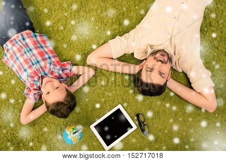 Top View Of Father And Son Lying On Green Carpet On Christmas