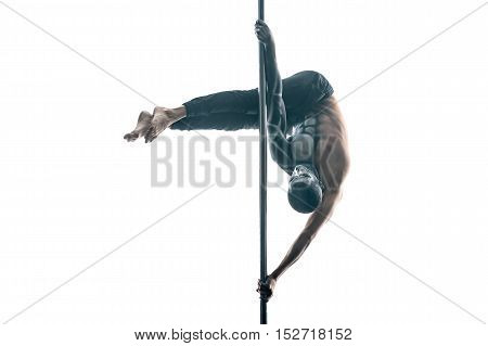 Sportive pole dancer with horrific body-art hangs upside down on a pylon in the studio on the white background. He wears black pants. His hands are on the pylon. Horizontal.
