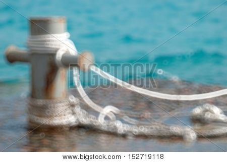 Rusty mooring bollard with ship ropes and clear turquouse sea ocen water Blurred bokeh background.