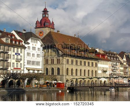 21 December 2012: Lucerne / Luzern, Switzerland. Riverbank Buildings And The Clock Tower With People