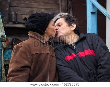 Man kisses a woman. People aged. Old wooden house