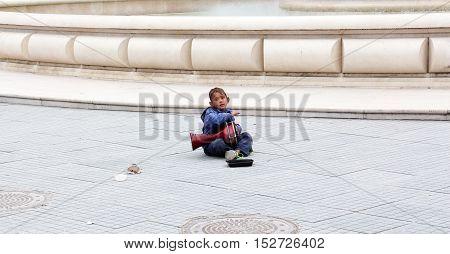 SKOPJE MACEDONIA - OCTOBER 18 2016:Roma boy singing and playing darbuka asking for money downtown of Skopjecapital of Macedonia