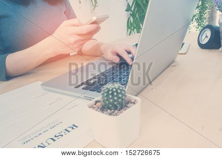 Office table with resume information and woman's hand hold smartphone tablet cell phone and find job Shopping online Office place on outdoor garden Vintage effect style pictures.