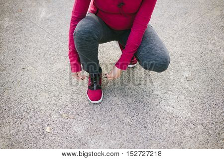 Detail of pregnant sporty woman lacing sneakers before jogging or training outdoor. Sport and healthy lifestyle during pregnancy concept
