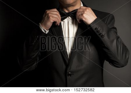 Close-up of gentleman wearing black tie straightens his bowtie on black