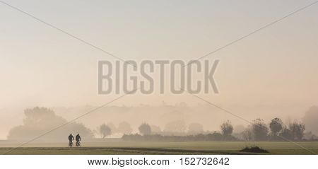 Morning with bicyclists in the fog during sunrise in the river forelands near the IJssel near Deventer Overijssel The Netherlands. poster