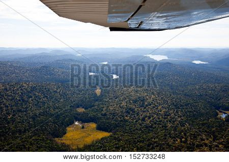 Adirondack forests, lakes, creeks and mountains aerial terrain view down from light aircraft