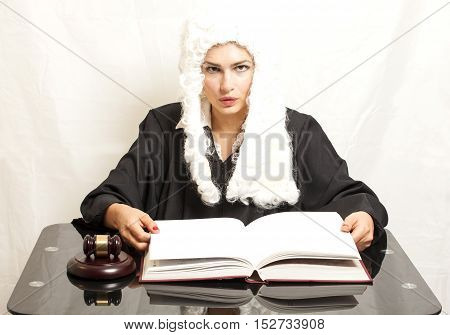 Female judge wearing a wig and black mantle with judge gavel and book on white background
