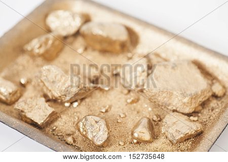Golden nuggets on grungy wash pan with sand on white background