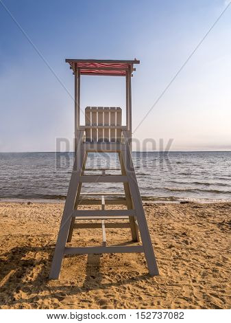 Empty wooden lifeguard post shot against the sea with clear blue sky