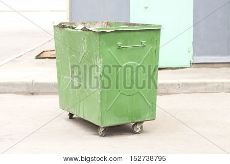 Green recycling container on street of city