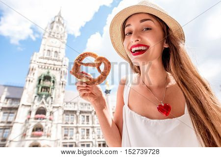 Young female tourist holding traditional bavarian bread called pretzel on the town hall building background in Munich, Germany