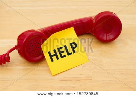 Calling to get help A retro red phone with yellow sticky note on a desk with text Help