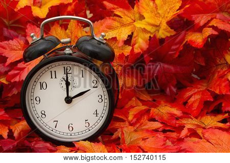 It is time for Autumn Some fall leaves and black and white alarm clock with copy-space