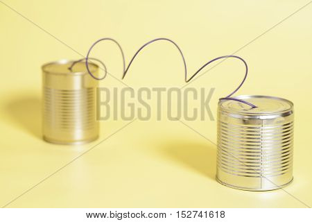 tin can phone on yellow .communication concept