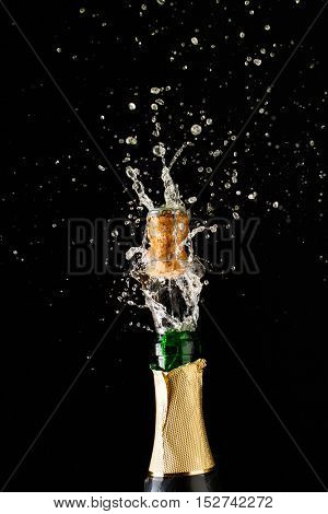 Cork flies out of champagne bottle. Festive theme