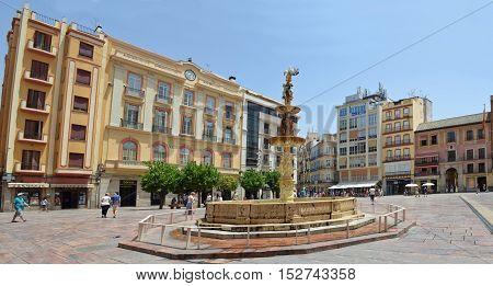 MALAGA, ANDALUCIA, SPAIN - JUNE 29, 2016: Plaza de la Constitucion fountain and shops Malaga Spain.