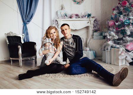 Christmas tree and happy family around indoors