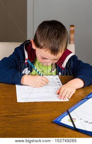 Boy doing homework in a living room.
