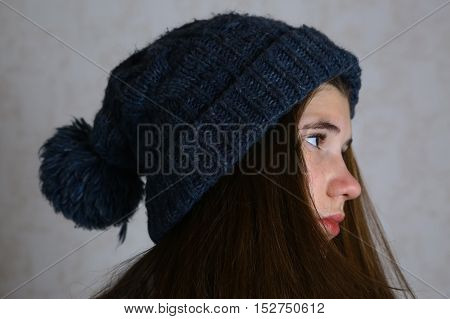 teenage girl in knitted blue hat with pompom close up portrait. Teen girl in winter hat.