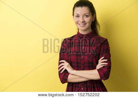 Portrait of young woman in red checkered dress standing with her arms crossed against yellow background and smiling. Mock up