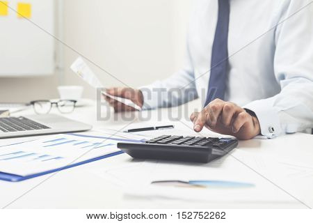 Man Using Calculator And Holding Document