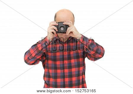 man with retro photo camera. elderly man looks into the camera viewfinder in search of the miraculous image.