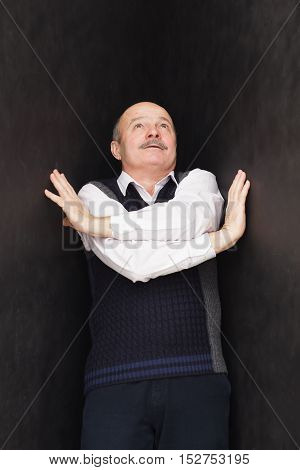 Elderly man pushes black walls. Negative emotions