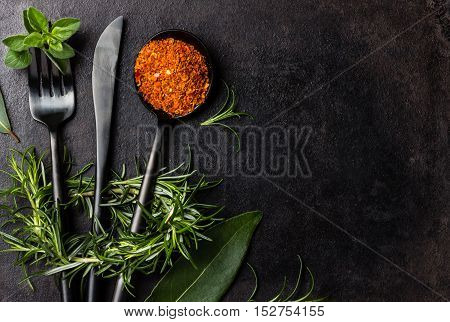 Food background with fresh herbs - rosemary and oregano, dryed spices - chili pepper, turmeric curcuma and black steel cutlery - knife spoon fork, tea spoon on black background. Top view. Copy space