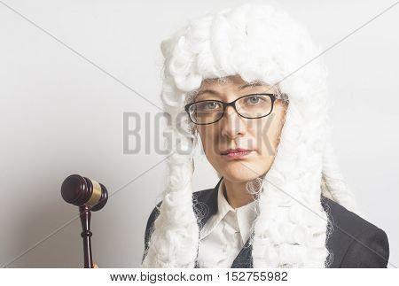 Female judge wearing a wig and Back mantle with eyeglasses holding judge gavel on white backgriund