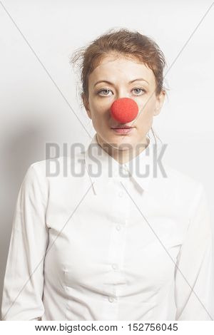Woman with red clown nose on white background