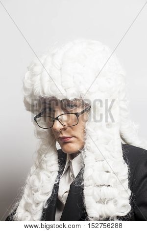 Female judge wearing a wig with eyeglasses on white