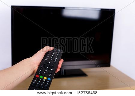 Hand using a remote control to turn off on on the TV with an empty screen